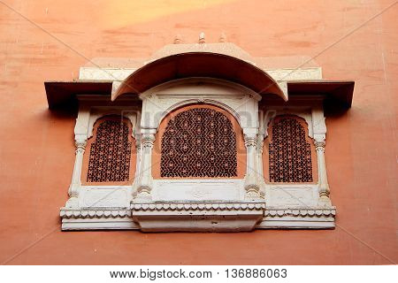 Concrete window frame with intricate design on red wall at Junagarh Fort Bikaner Rajasthan India Asia