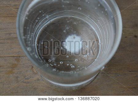 antacids in water glass on wooden table