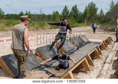 Tyumen, Russia - June 11, 2016: Race of Heroes project on the ground of the highest military and engineering school. Participants carry out anti-gravitation exercise. The girl has fallen in water