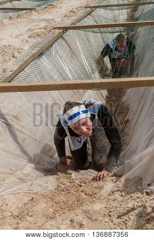 Tyumen, Russia - June 11, 2016: Race of Heroes project on the ground of the highest military and engineering school. Guardroom stage. Girl leaves entrenchment with sand and water under net