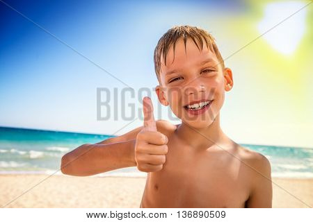 little cude kid with thumb up on the sea