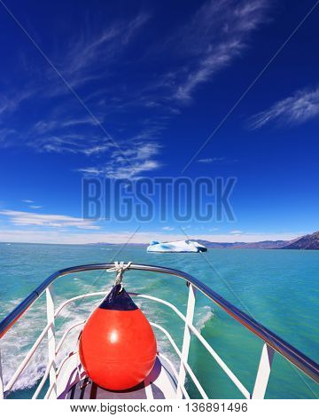 White-blue huge icebergs float near a ship board. Ice and sun Patagonia. Excursion on the tourist boat on Lake Viedma
