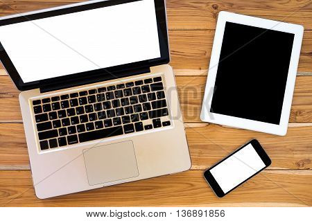 Office workspace with blank screen laptop blank screen tablet and blank screen smartphone. Top view office gadgets.