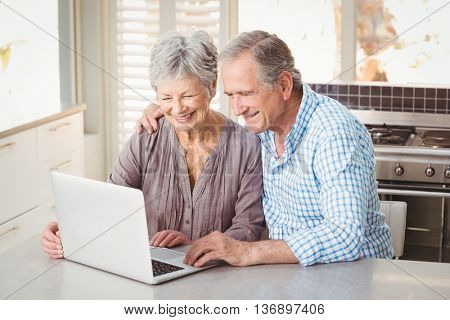Cheerful senior couple using laptop while sitting in kitchen