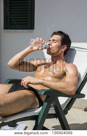 Shirtless Young Man Drying Off in Hot Sun, Drinking Water from Plastic Bottle, Muscular Man Wearing Bathing Suit Sunbathing on Beach Lounge Chair