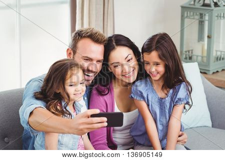 Family smiling while taking selfie on mobile phone at home