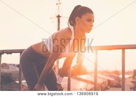 Tired after jogging. Beautiful young woman in sports clothing bending and looking tired while standing on the bridge with evening sunlight and urban view in the background