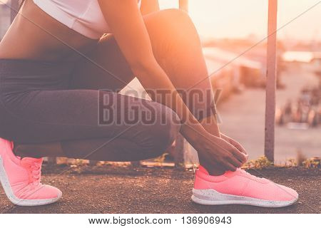 Tying shoelaces. Close-up of young woman in sports clothing tying her shoelaces while standing on the bridge with evening sunlight and urban view in the background