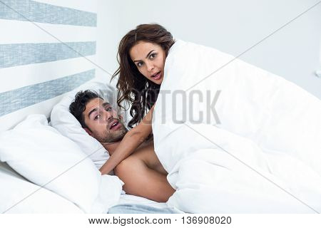 Portrait of surprised young couple enjoying on bed in room