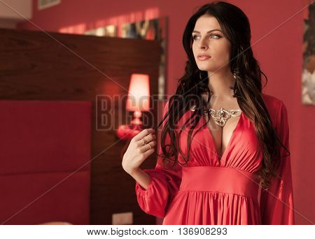 Elegant lady. Fashion beautiful sensual brunette woman with makeup in luxurious prom dress with bijou, posing on modern armchair with sliver frames.