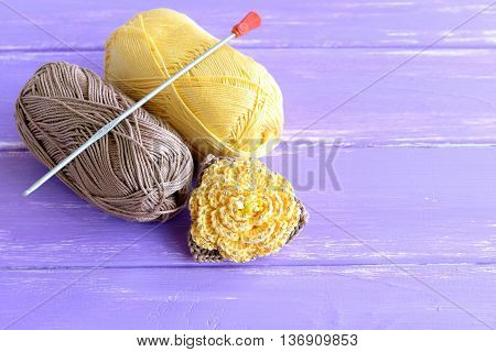 Handmade yellow and brown crochet flower decorated with beads. Two skeins of cotton yarn and crochet hook on lilac wooden background. Easy knitting project for beginners