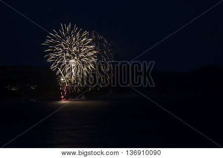 Fireworks set off on raft in sea with reflections - with copy / text space.