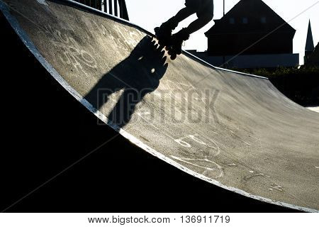 Feet of a rollerblader with inline skates riding over the concrete halfpipe in an outdoor skate park dramatic backlit shot with hard shadows nearly black and white copy space selected focus motion blur