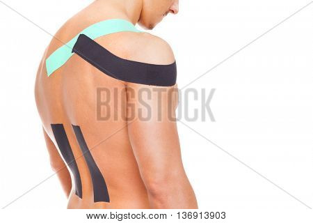 Man with kinesiotaping on the shoulder and lower back, isolated on white background