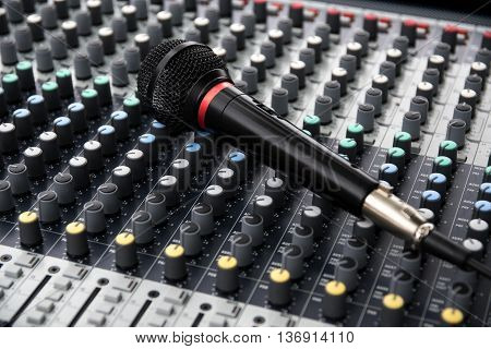 microphone on a professional sound mixing console with adjusting knobs music device for audio signal