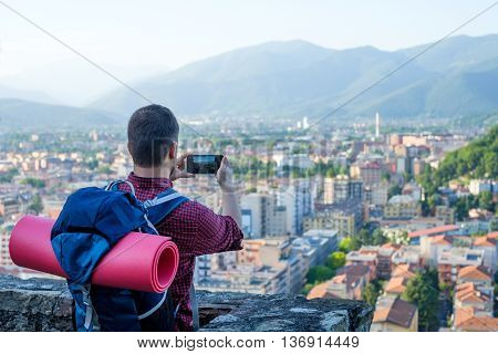 Man with backpack taking a picture of a cityscape