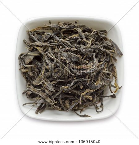 Organic Green Tea (Camellia sinensis) dried long leaves in white ceramic bowl isolated on white background. Macro close up. Top view.