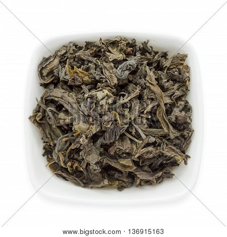 Organic Green Tea (Camellia sinensis) dried whole leaves in white ceramic bowl isolated on white background. Macro close up. Top view.