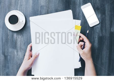 Female hands holding blank paper sheets over wooden desktop with blank white smartphone and coffee cup. Mock up