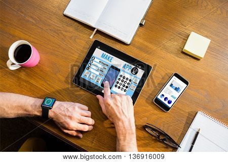 Make your own app smartphone against businessman using a tablet computer