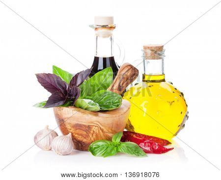 Fresh garden herbs in mortar, olive oil, vinegar. Basil, rosemary, dill. Cooking ingredients. Isolated on white background