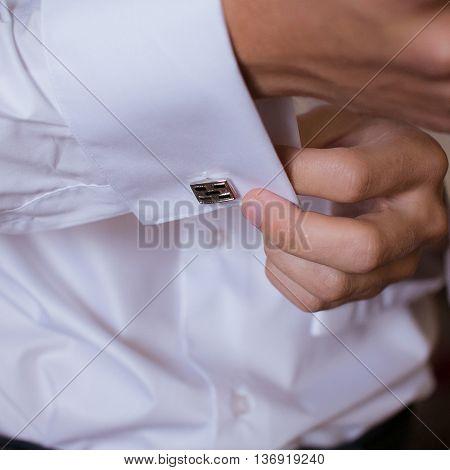 Hands of wedding groom getting ready in suit