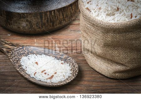 Rice in small sack on dark wooden table