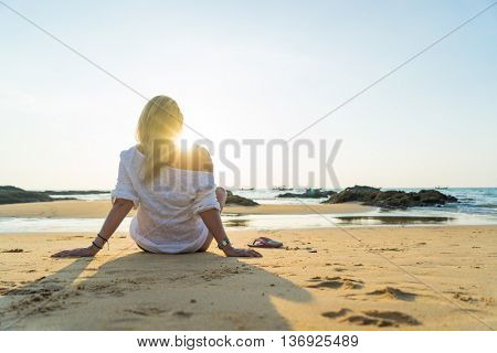 Happy woman  relaxes and enjoys the sunset over the sea sitting on the beach