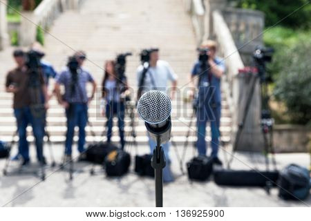 Microphone in focus against blurred camera operators and reporters. Broadcast journalism.