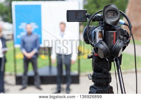 News conference. TV broadcasting. Filming press conference with a video camera.