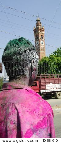 "A man drenched in colors on the day of ""holi"" in the foreground of ghantaghar the landmark clocktower of lucknow India poster"
