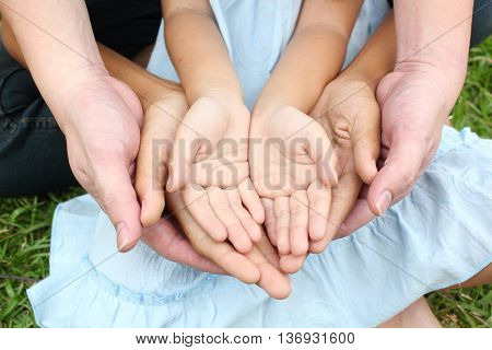 Adult hands holding kid hands in the park.