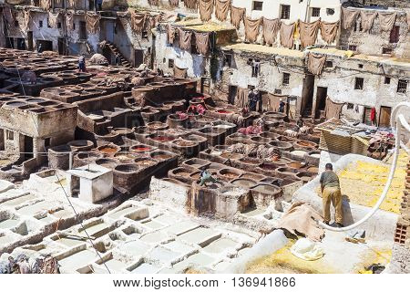 FEZ MOROCCO - JUNE 10. 2016: Workers at the Chouwara tannery in Fez Morocco.