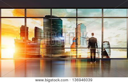 Businessman in interior standing in front of huge panoramic window looking at city with sunlight. Research concept