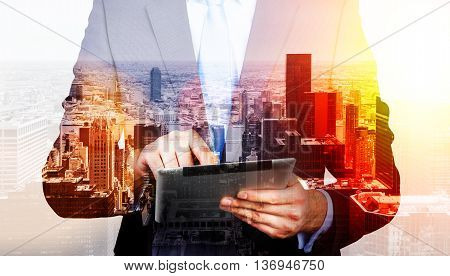 Businessman using tablet on New York city background with sunlight. Double exposure