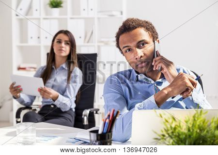 Young business man and woman using tablet and talking on phone in office. Concept of teamwork. Office interior in the background