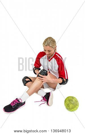 Sportswoman wearing a knee pad on white background