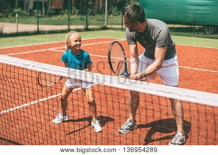Tennis training. Cheerful father in sports clothing teaching his daughter to play tennis while both standing on tennis court