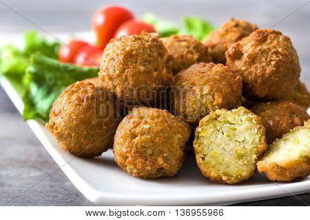 Vegetarian falafels and vegetables on a rustic wooden table