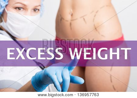 excess weight written on a virtual screen. Internet technologies in medicine concept. medical doctor presses a finger on a virtual screen. cosmetic surgery, lifting and breast augmentation.