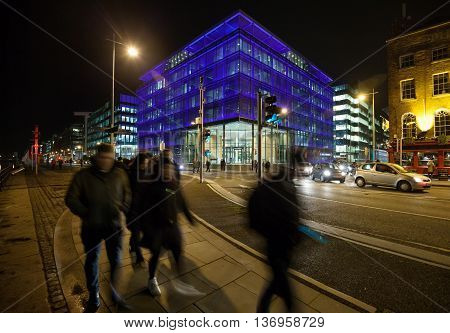 City Street busy with pedestrians and office buildings during the night. Dublin
