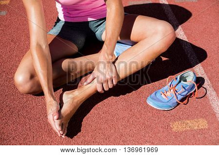 Female athlete with foot pain on running track on a sunny day