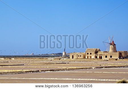 Salt evaporation ponds and windmill in Stagnone lagoon, Marsala, Sicily