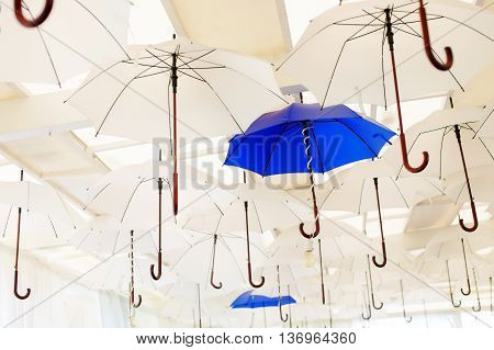umbrellas and lamps under a ceiling. white and blue umbrellas disclosed under a ceiling of the restaurant as an element of interior design