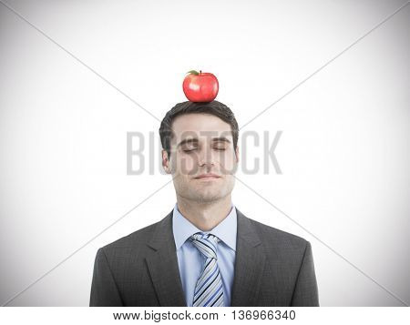 Handsome businessman with eyes closed against red apple