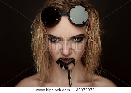 Agressive female Model with black Paint Drips from her Mouth