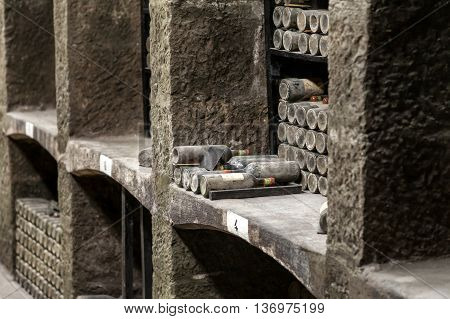Stone shelves with expensive vintage wine bottles covered with dust