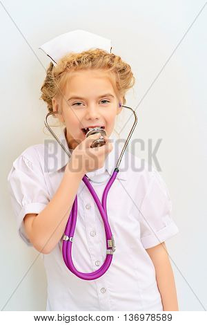 Pretty little girl playing a doctor. Different occupations. Children's Health, Pediatrics. Isolated over white.