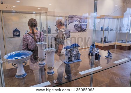 VELIKY NOVGOROD RUSSIA-JULY 1 2016. Unidentified museum visitors looking the exhibition of Chinaware in the traditional Russian style at the Museum of Fine Arts