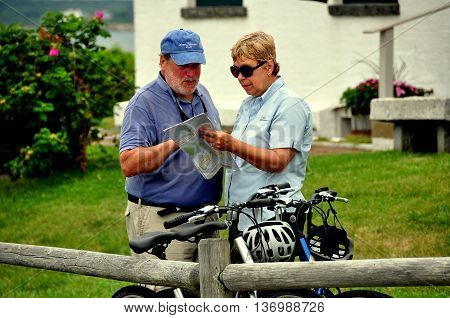 Jamestown Rhode Island - July 18 2015: Man and woman next to their parked bicycles study a road map at 1856 Beavertail State Park Lighthouse on Conanicut Island